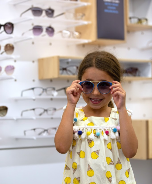 young girl tries on glasses at eyeconic store